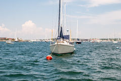 Boat docked in bay. Open water with  sailboat anchored. Stock Photo
