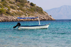 Boat docked on little beach - croatia. A small boat in the crystal clear water of a bay stock photo