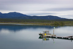 Boat docked in quiet mountain lake, Yukon, Canada. On a calm, cloudy day, a row of boats along a dock are reflected in the still waters of a lake, with the Stock Images