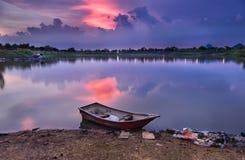 Boat docked on river in beatiful twilight sky
