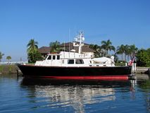 Boat docked in South Florida. A picture of a boat, docked in a south Florida marina. The waters are calm and palm trees can be seen in the background Stock Image
