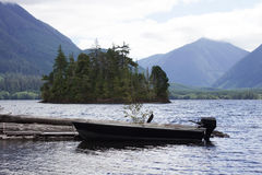 Boat Docked on Victoria Lake. A small motor boat on Victoria Lake in Port Alice, BC, with a mountain background Royalty Free Stock Photos