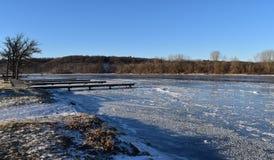 Boat docks on frozen river Royalty Free Stock Image