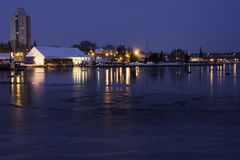 Boat docks and harbor lights reflecting in partially frozen lake Stock Photography