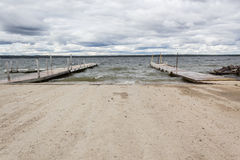 Boat docks at the lake. Two boat docks on the lake under cloudy sky Stock Photos