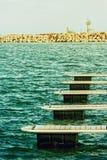 Boat docks in sunlight near stone dam Stock Photo