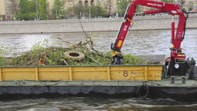 Boat  dragging trees across river urban surrounding. Industrial transporter Moskva river Moscow Russia moving shot stock video footage