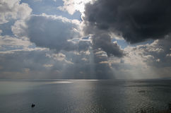 Boat and dramatic clouds over the sea Stock Images