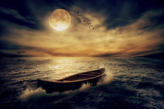 Boat drifting away from past in middle of ocean after storm without course. On moonlight sky night skyline clouds background. Conceptual nature landscape screen Stock Photo
