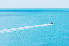 Boat Driving Into The Deep Sea. Lonely Boat Driving Into The Deep Sea On A Bright Summer Day Stock Photo