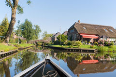 With boat in Dutch village. Dutch village Giethoorn with water and bridges stock photos