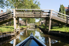 With boat in Dutch village. Dutch village Giethoorn with water and bridges royalty free stock photo
