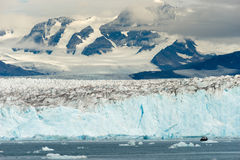 Boat Dwarfed by Mountains Glaciers Alaska Kenai Fjords royalty free stock photos