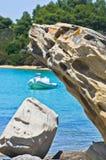 Boat at emerald green sea water near coast of small uninhabited island near coast of Sithonia Royalty Free Stock Photo