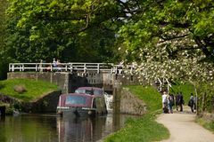 Boat emerges from Hirst Lock, Yorkshire. Canalside walkers look on as a boat emerges from the Hirst Lock on its way towards World Heritage Site, Saltaire, on the stock photo