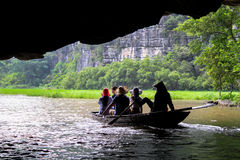 Boat emerging from a Cave. A boat full of people emerges from the dark of a cave, into the sunlight.  Nature abound in Tam Coc, Vietnam Stock Photography