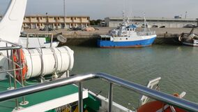 the boat enters the port, seen from the stern of other boats waiting to set sail and work at sea fishing