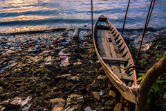 A boat and evening tide on messy riverbank at sunset Royalty Free Stock Images