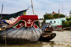 Boat with eyes and anchor painting decoration on the prow, anchored in the muddy waters of the Mekong Delta, Vietnam. Wooden boat  with a motocycle on the deck stock photography