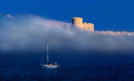 Boat facing a storm in the mediterranean sea. Storm approaching Le Chateau d`If in Marseille France on an overcast day royalty free stock photography