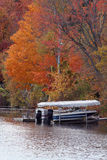 Boat in the Fall. Colorful fall foliage along a Vermont lake shore Royalty Free Stock Image