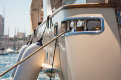 Boat fenders. Fenders hanging on the side of a white yacht which is in the port on a sunny day with other ship masts in the background Royalty Free Stock Photos