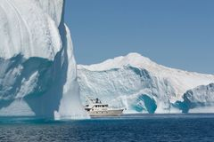 A boat finding its way through the Arctic. Arctics icebergs compete with a fiberglass boat stock image