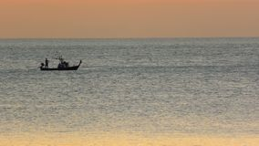 Boat with fishemen at sunset stock footage