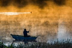 Boat and fisherman in a misty foggy sunny orange lake