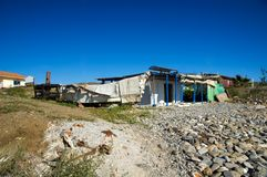 Boat and fisherman's house. Unused sailing boat covered with cartons and fisherman's old house on stony beach royalty free stock image