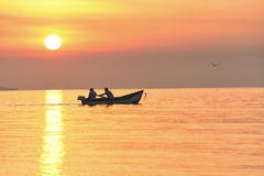 Boat with fishermen in the sea at sunrise, sunset Stock Photos
