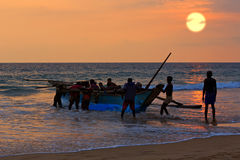 Boat with fishers on sunset background Royalty Free Stock Image
