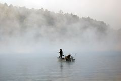 Boat fishing in the fog. Two men fishing in the fog that obscures the mountain behind them Stock Images