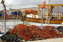 Boat and Fishing Nets. Fishing nets lay next to a boat in a Southern Turkey harbor Stock Image