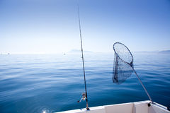 Boat fishing rod and landing net in sea Royalty Free Stock Image
