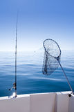 Boat fishing rod and landing net in sea Royalty Free Stock Images