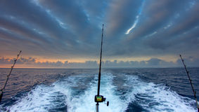 Boat fishing rods. Over a beautiful cloudy seascape stock photography