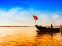 Boat with flag in ganga river at banaras india. With blue sky royalty free stock image