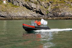 A boat with a flag. Two fishermen sail on a motor boat. stock images
