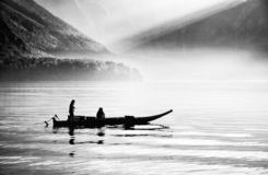 Boat floating on the famous Hallstatt lake in a autumn foggy morning royalty free stock photo