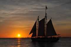 Boat floating in front of the sunset Florida. Sailing ship in front of a floridian sunset, keys islands Royalty Free Stock Images