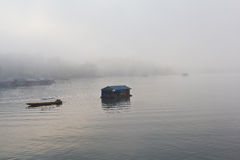 Boat and floating house in the mist Royalty Free Stock Photos