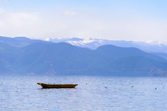 A Boat Floating On The Lake. Peaceful moment beside Lugu Lake. In the distance are continuous snow mountains stock images