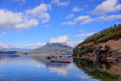 A Boat Floating On The Lake. Peaceful moment beside Lugu Lake. In the distance are continuous snow mountains royalty free stock photo