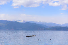 A Boat Floating On The Lake. Peaceful moment beside Lugu Lake. In the distance are continuous snow mountains royalty free stock image