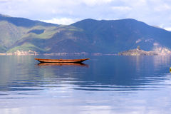 A Boat Floating On The Lake. Peaceful moment beside Lugu Lake. In the distance are continuous snow mountains royalty free stock photos