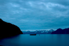 Boat Floating on Ocean Landscape with Blue Midnight Alaskan Ligh. A boat floats in the ocean off the coast of Seward, Alaska with mountains in the distance Royalty Free Stock Photo