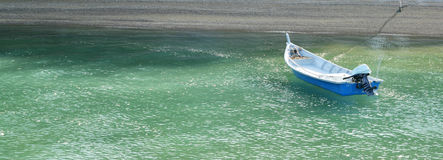 Boat floating on the sea near beach Stock Image