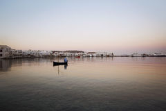 Boat Floating at Sunrise. Sunrise in Mykonos with boat floating on the water. Sunrise is pink and colorful Royalty Free Stock Photos
