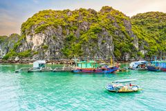 Boat at floating village of fishers and fish or oyster farmers in Halong Bay, Vietnam royalty free stock photo